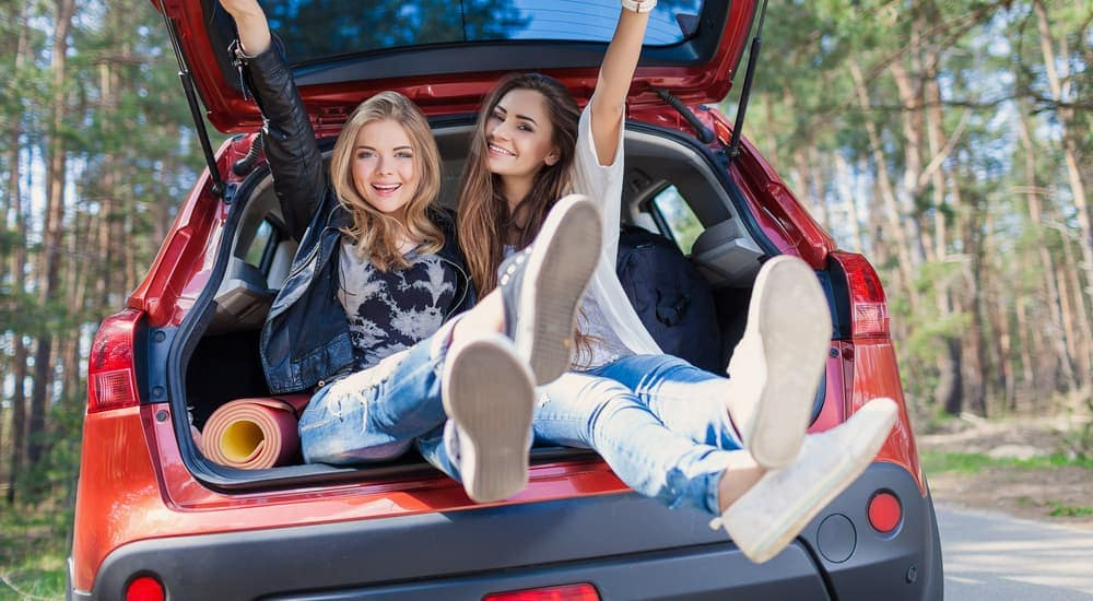 Two girls are sitting in the trunk of a red car.