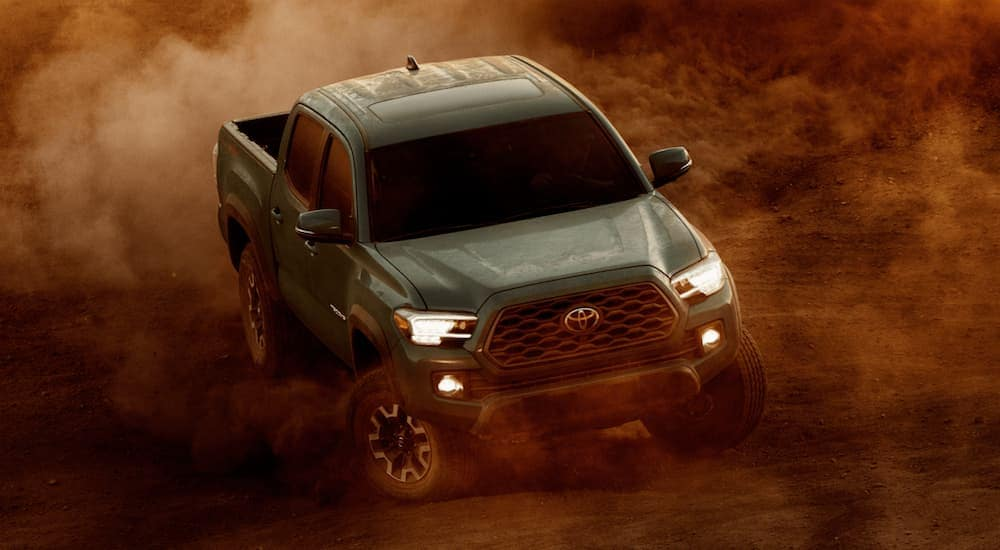 A green 2021 Toyota Tacoma is off-roading in dirt.