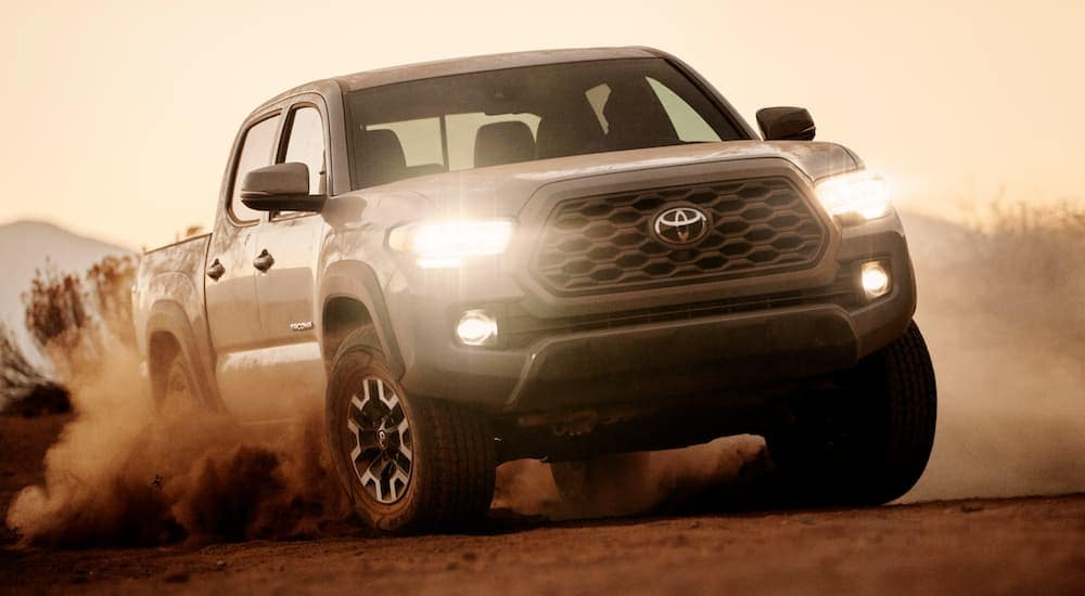 A grey 2021 Toyota Tacoma is off-roading in dirt after leaving a Toyota Truck dealer near me.