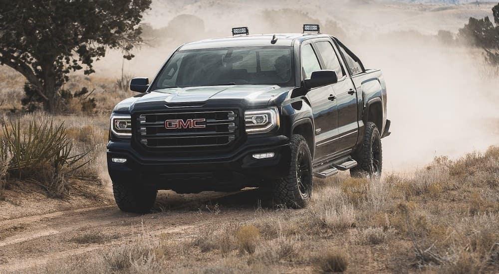 A black 2017 GMC Sierra 1500 is off-roading on a dirt trail.