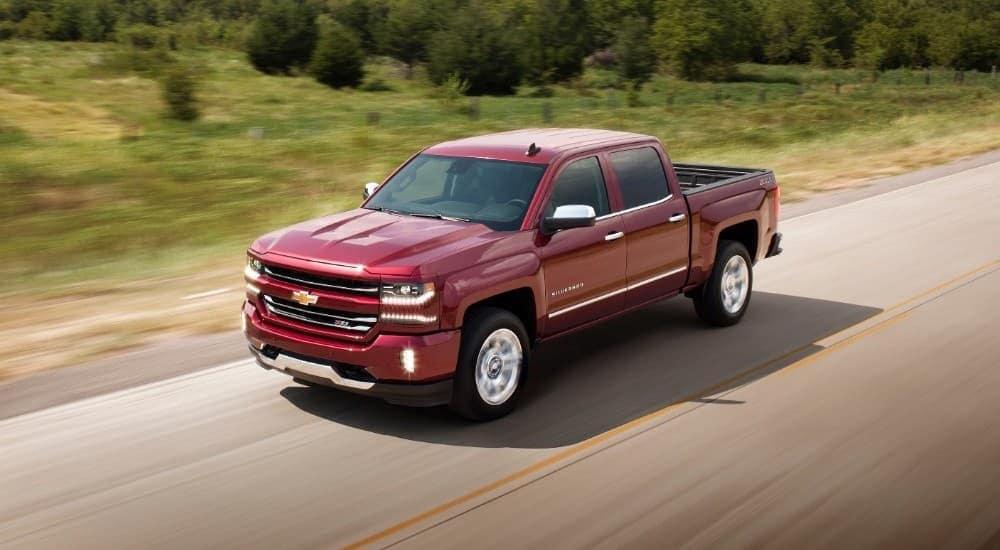 A popular used truck for sale in PA, a red 2018 Chevy Silverado 1500, is driving on a road past grass and trees.