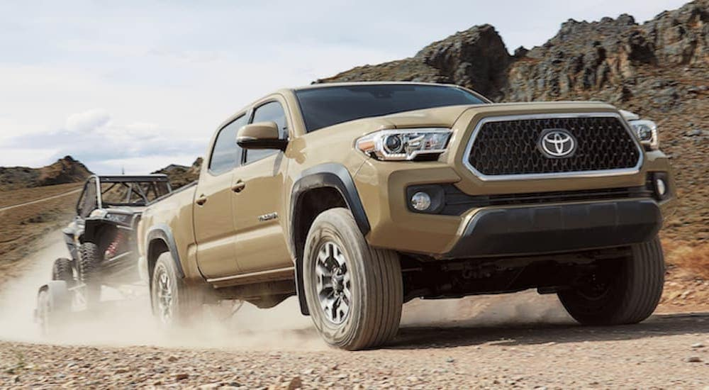 A tan 2019 Toyota Tacoma is towing a side-by-side on a dirt road in the desert.