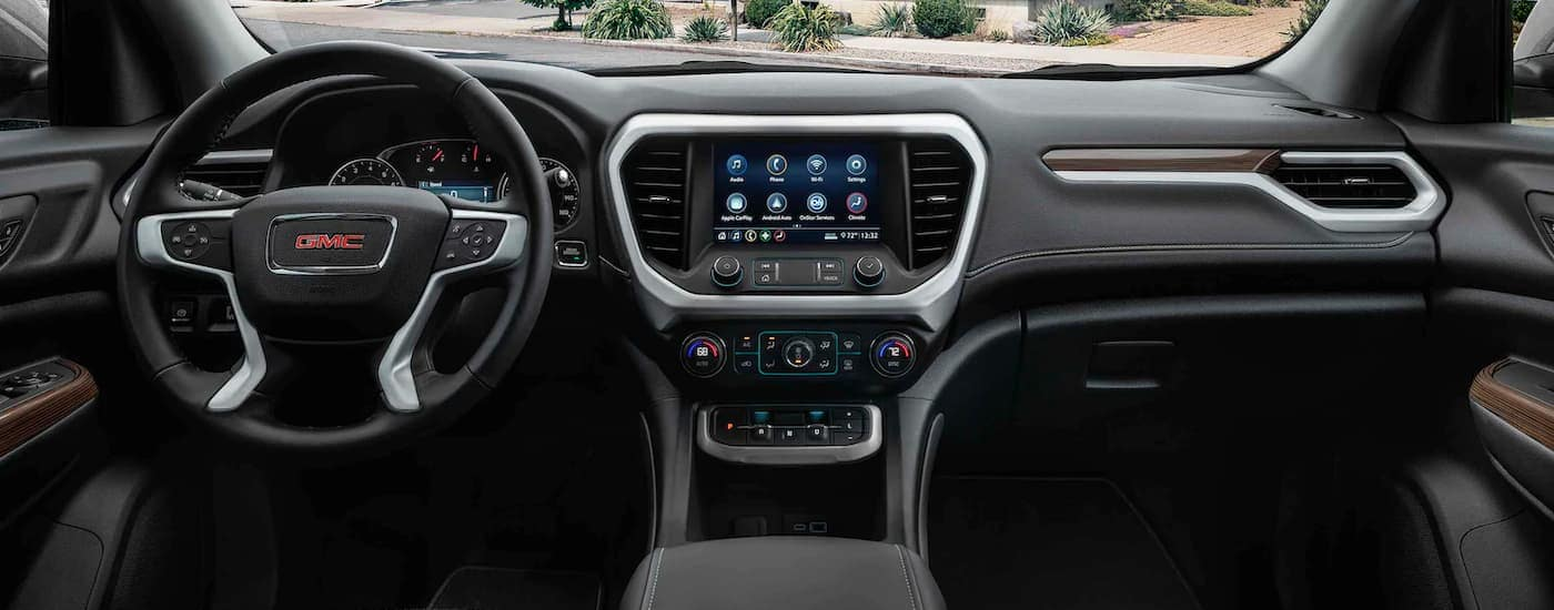 A close up shows the infotainment screen and black interior on a 2021 GMC Acadia.