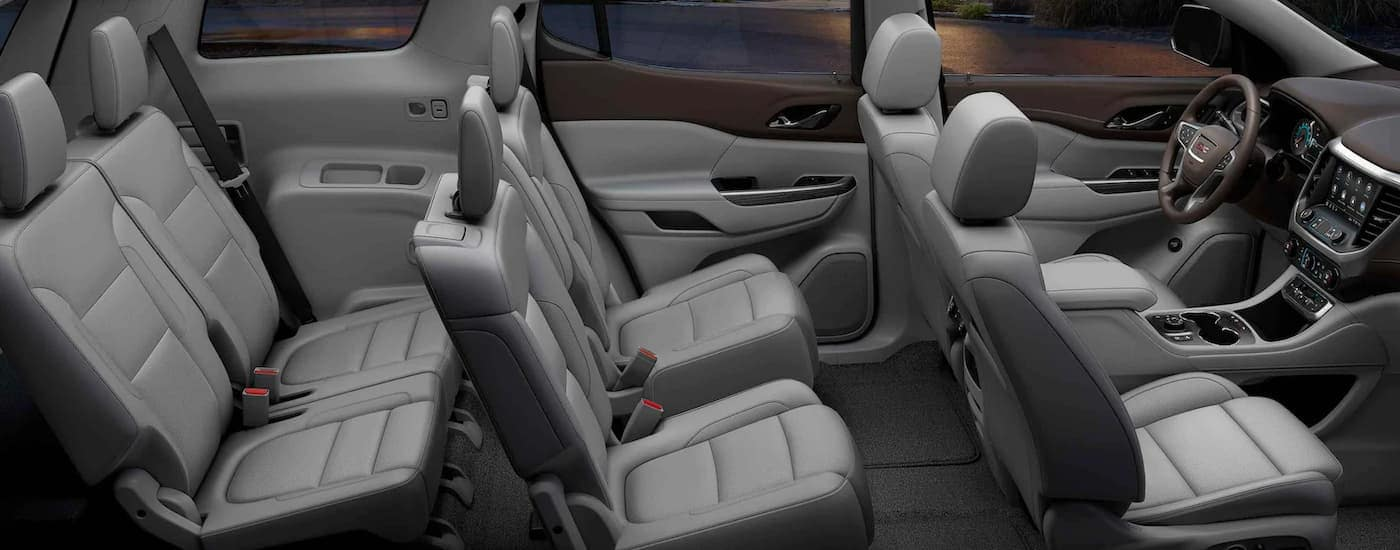 Three rows of gray seats are shown from the passenger side on a 2021 GMC Acadia.