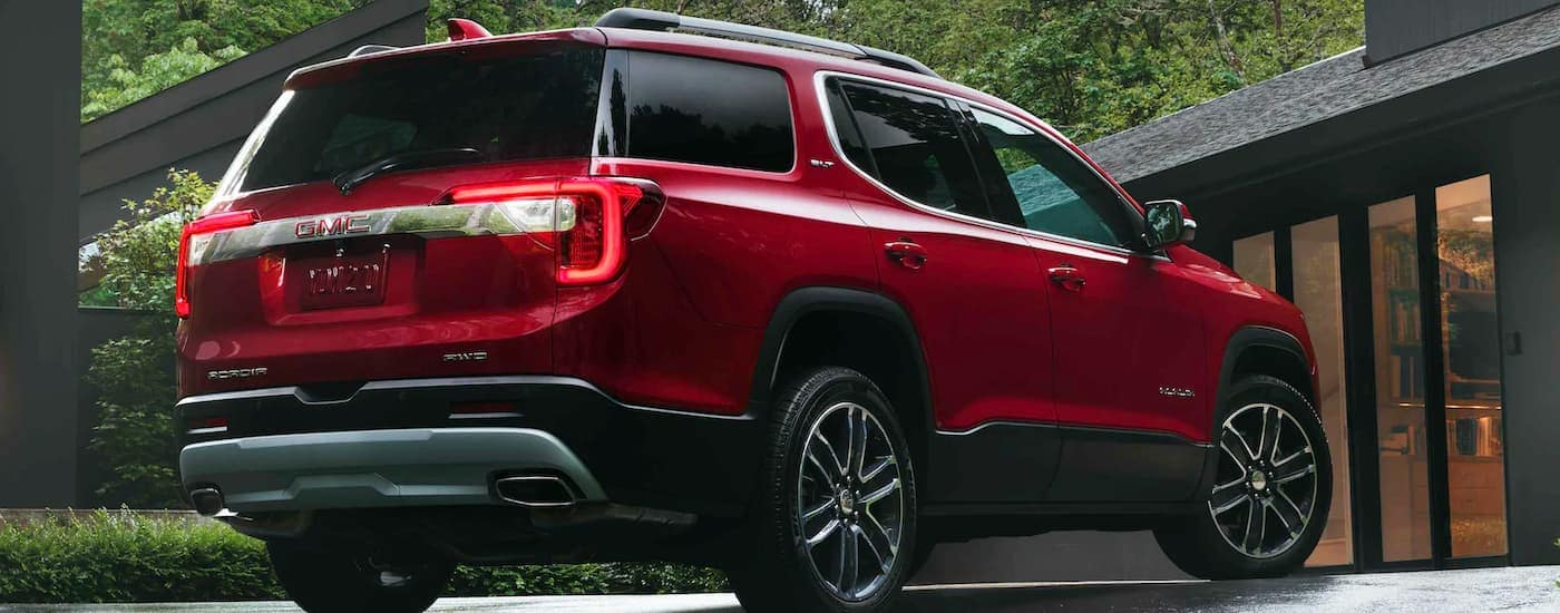 A red 2021 GMC Acadia is shown from the rear parked in the driveway of a modern home.