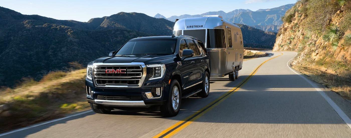 A black 2021 GMC Yukon is driving down a mountain road while towing an airstream trailer.