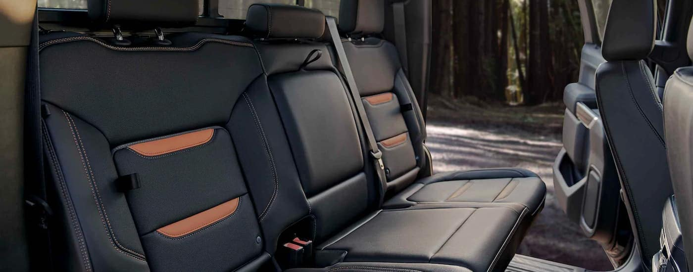 A close up shows the black and orange rear leather seats in a 2021 GMC Sierra 2500HD AT4.