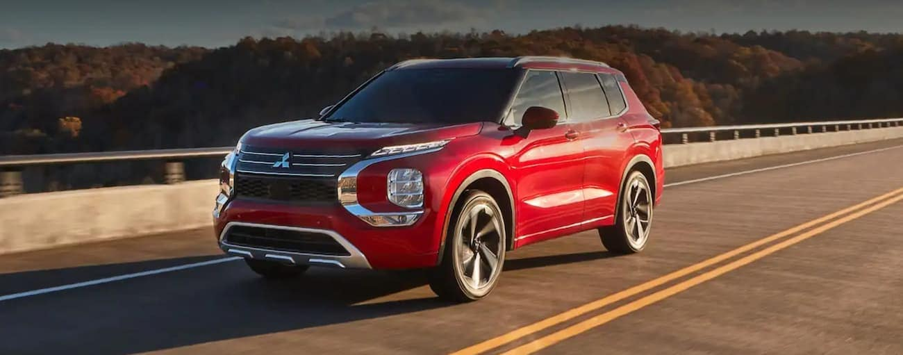 A red 2022 Mitsubishi Outlander is driving on a road up high with trees behind it.