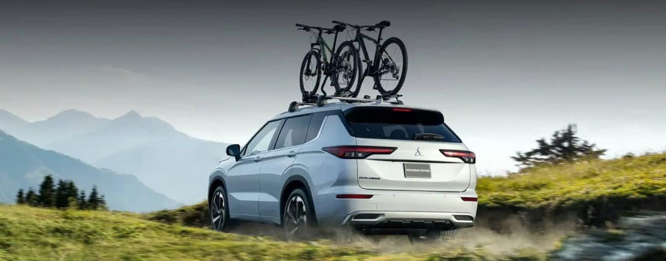 A white 2022 Mitsubishi Outlander with bikes on the roof is driving on a dirt path toward mountains.