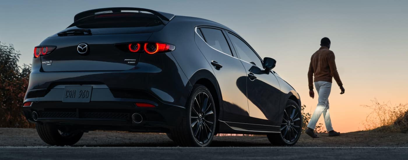 A man is walking away from a grey 2021 Mazda 3 Hatchback shown from a low angle at dusk.