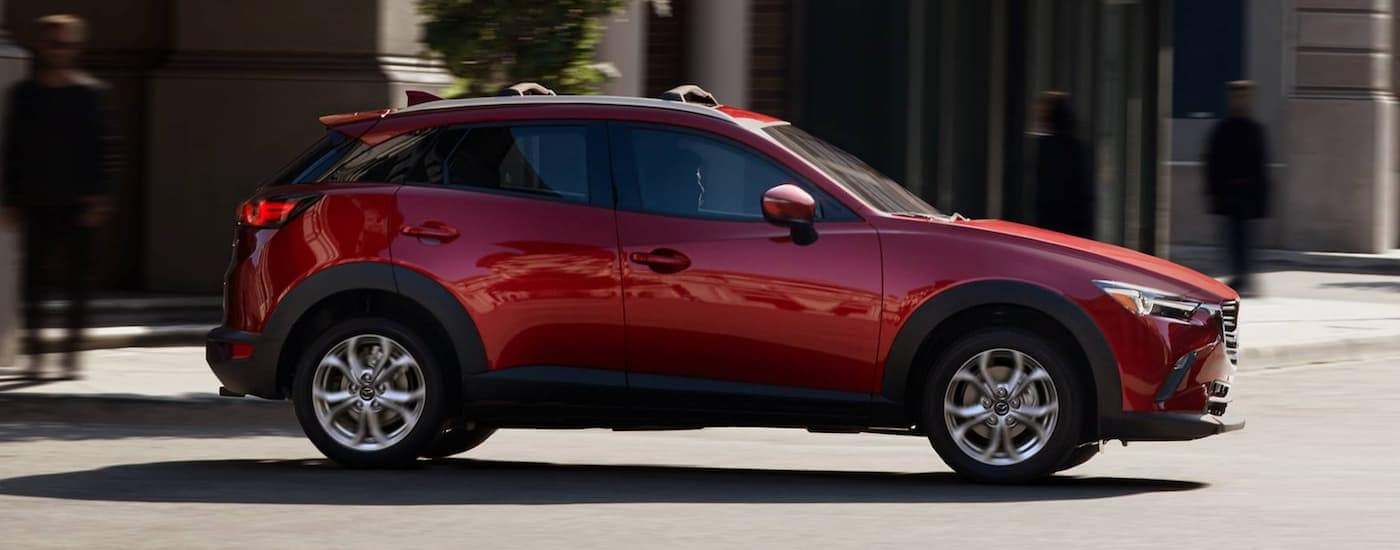 A red 2021 Mazda CX-3 is shown from the side driving on a city street.
