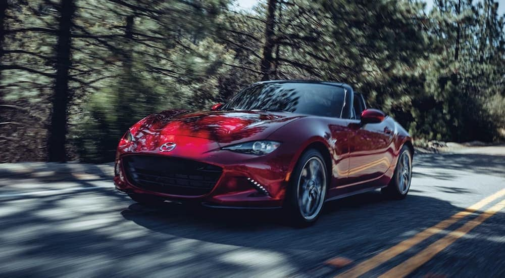 A red 2021 Mazda MX-5 Miata is driving on a tree-lined road after leaving an Indiana, PA, Mazda dealer.
