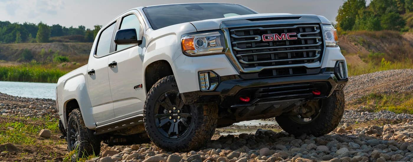 A white 2021 GMC Canyon AT4 is parked on rocks with a lake in the background.