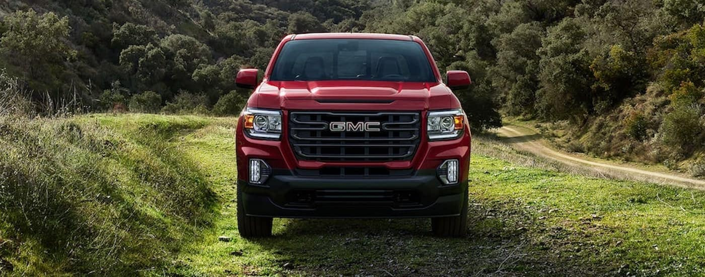 A red 2021 GMC Canyon Elevation is shown from the front in a green valley.