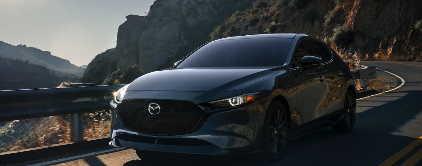 A gray 2021 Mazda3 hatchback is shown from the front driving down a windy mountain road.