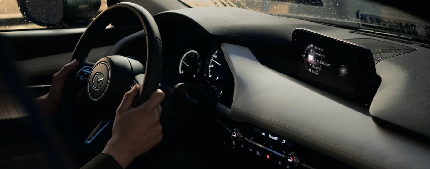 A close up shows hands on a steering wheel and the infotainment screen on a 2021 Mazda3 sedan.