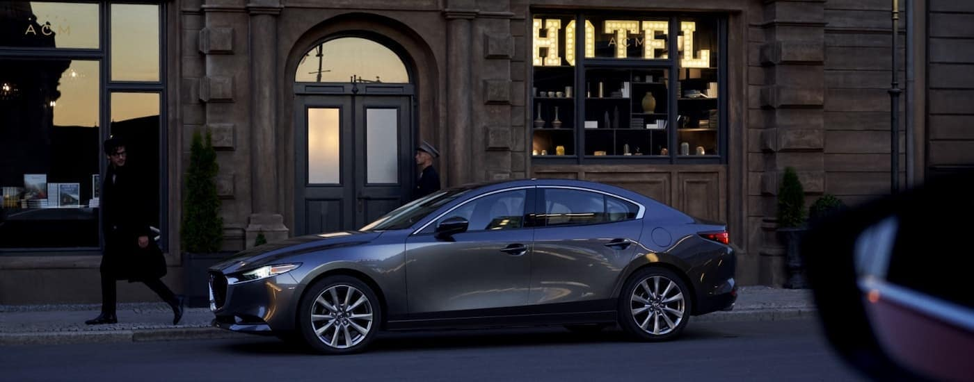 A grey 2021 Mazda3 sedan is shown from the side parked outside of a hotel.