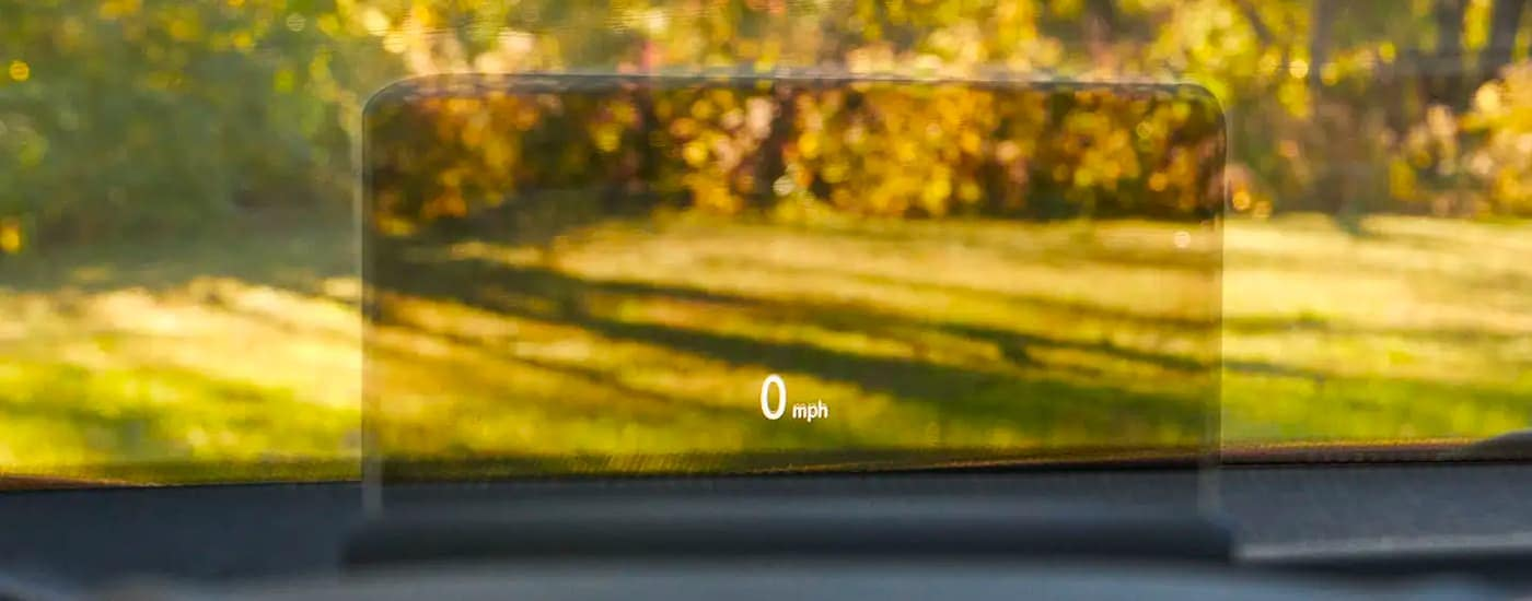 A close up shows the heads up display screen showing 0 mph.