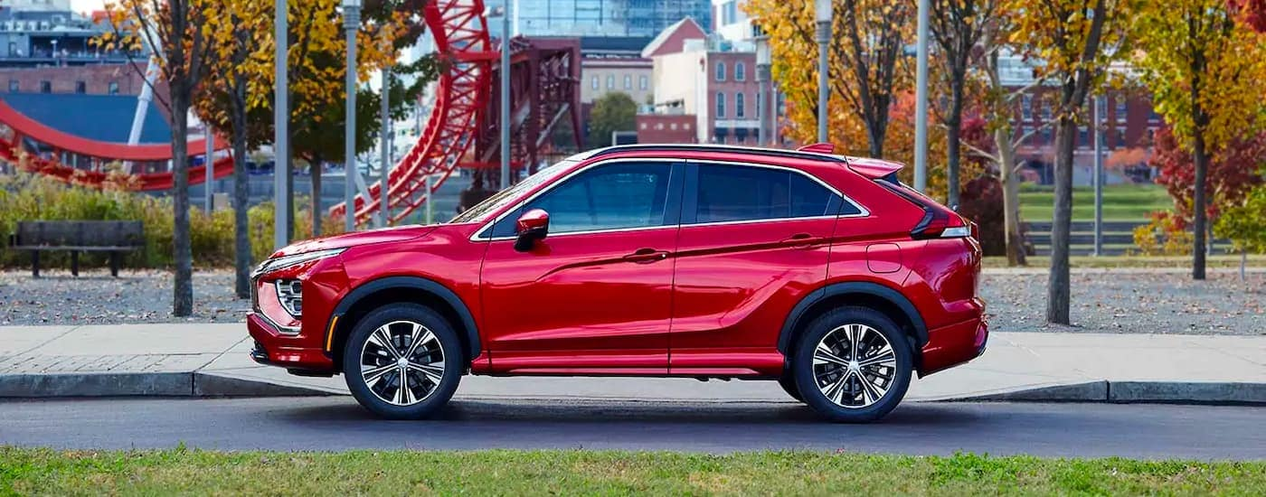 A red 2022 Mitsubishi Eclipse Cross is shown from the side parked in front of a theme park.