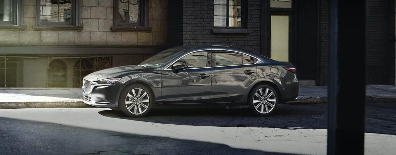 A grey 2021 Mazda 6 Sport is shown from the side parked on a city street.