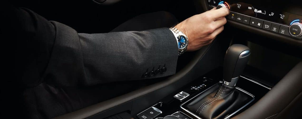 A close up shows a person adjusting the climate controls in a 2021 Mazda 6.