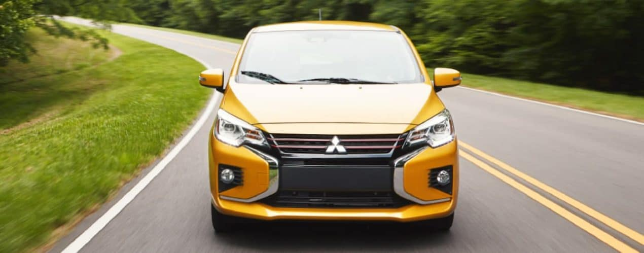A yellow 2021 Mitsubishi Mirage is shown from the front driving down an empty road.
