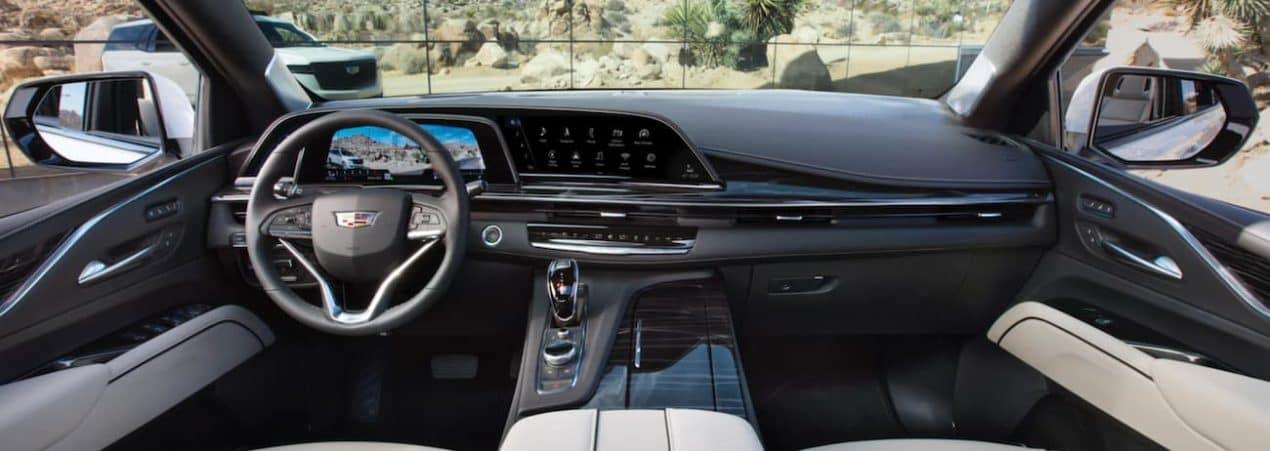 The black interior of a 2021 Cadillac Escalade shows the steering wheel and infotainment screen.