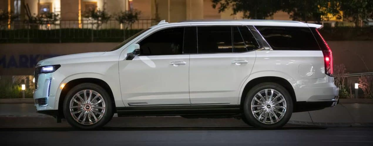 A white 2021 Cadillac Escalade is shown from the side parked on a city street.