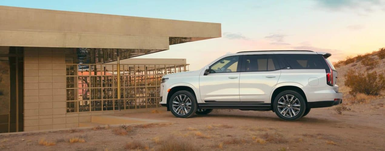 A white 2021 Cadillac Escalade is parked at a modern house in the desert.