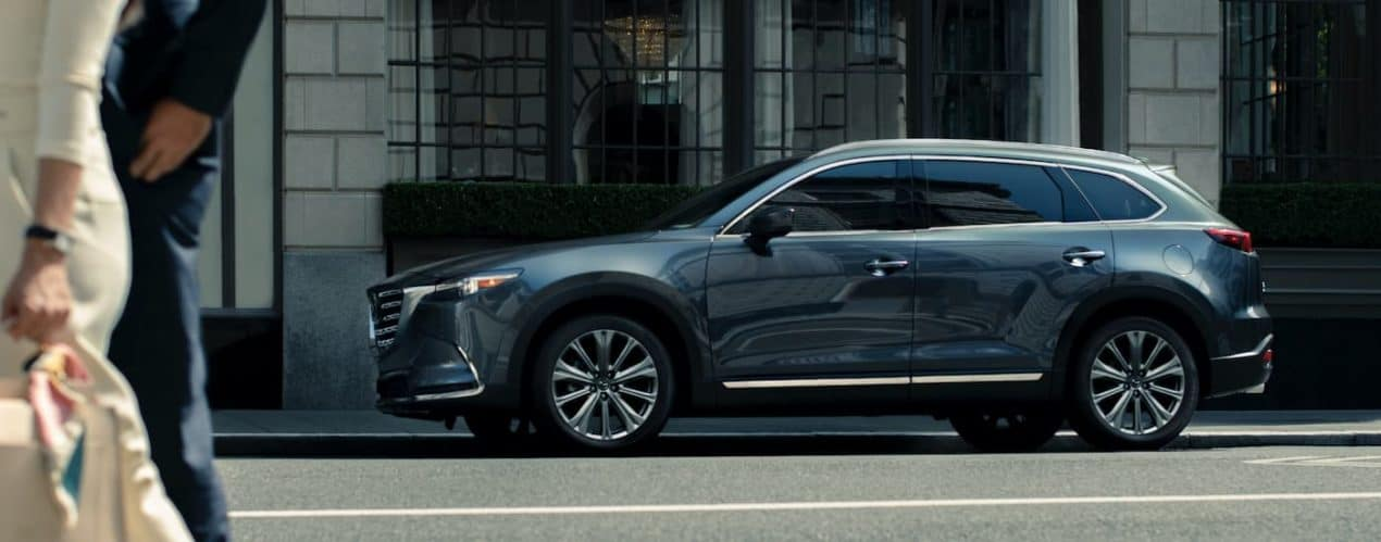 A grey 2021 Mazda CX-9 is shown from the side parked on a city street.