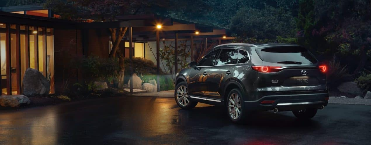 A dark grey 2021 Mazda CX-9 is shown at night parked in front of a modern house.