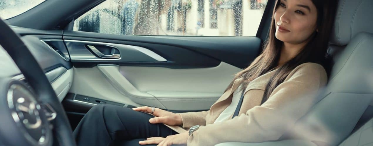 A woman is shown sitting in the interior of a 2021 Mazda CX-9.