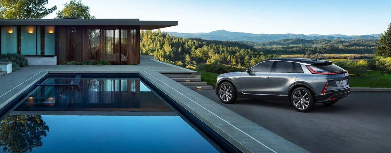 A silver 2023 Cadillac Lyriq is parked next to a house and pool.