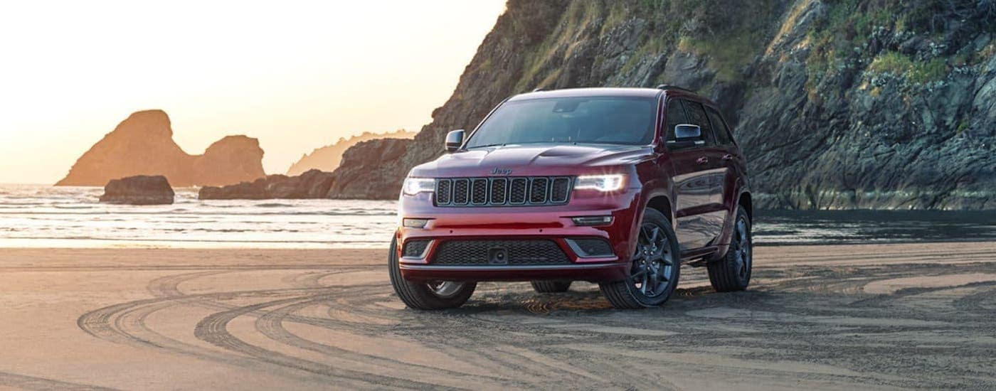 A red 2020 Jeep Grand Cherokee is parked on a beach at sunset.