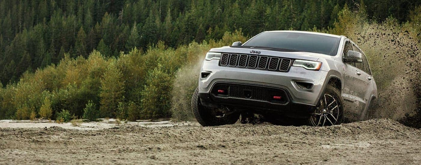 A silver 2020 Jeep Grand Cherokee Trailhawk is kicking up dirt on a track near Lexington, KY.