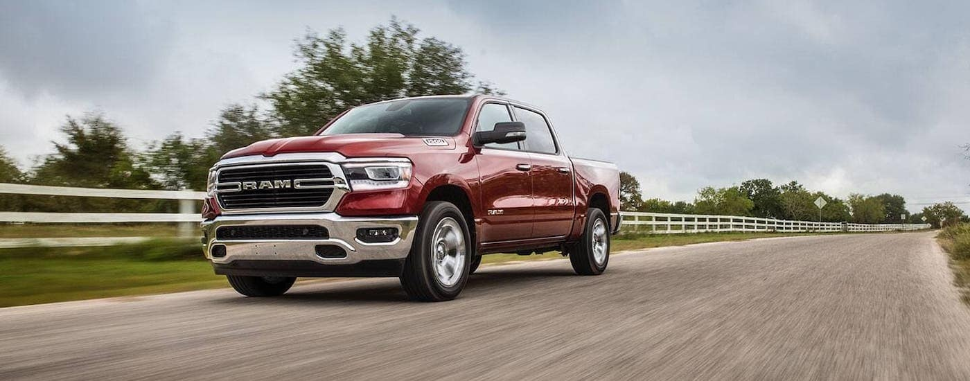 A red 2020 Ram 1500 is driving on a highway with a white fence.