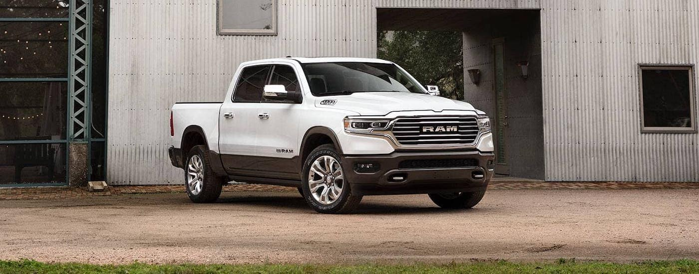 A white 2020 Ram 1500 is parked in front of a metal warehouse near Lexington, KY.