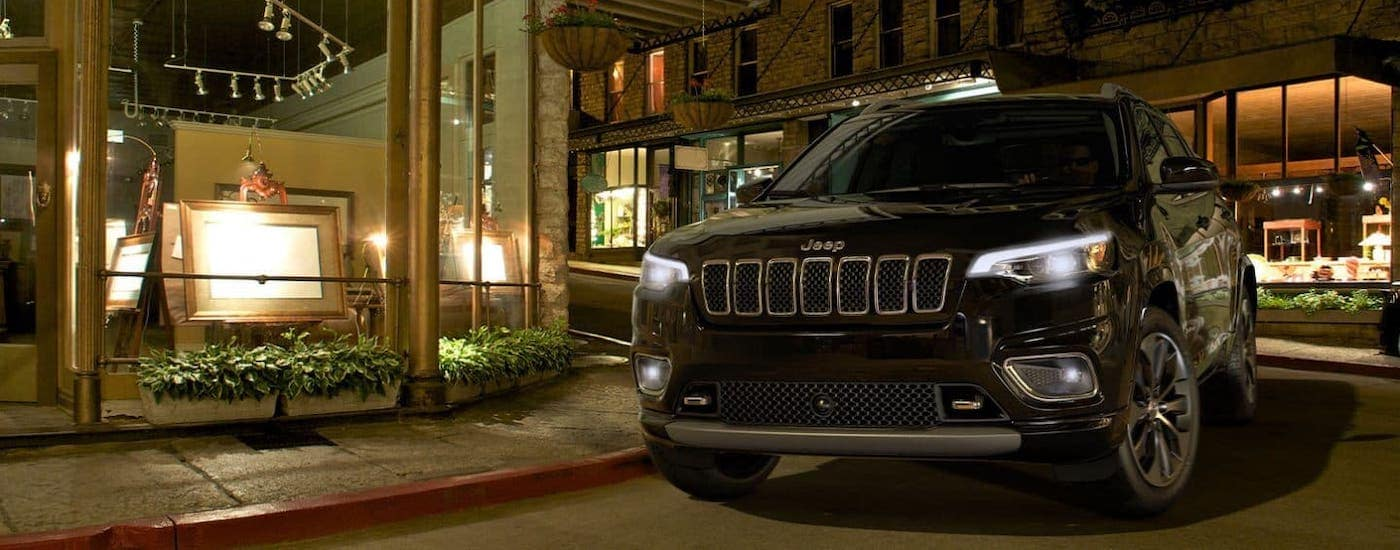 Our top pick for used cars and SUVs, a black 2018 Jeep Cherokee, is parked in front of an art gallery near Lexington, KY.