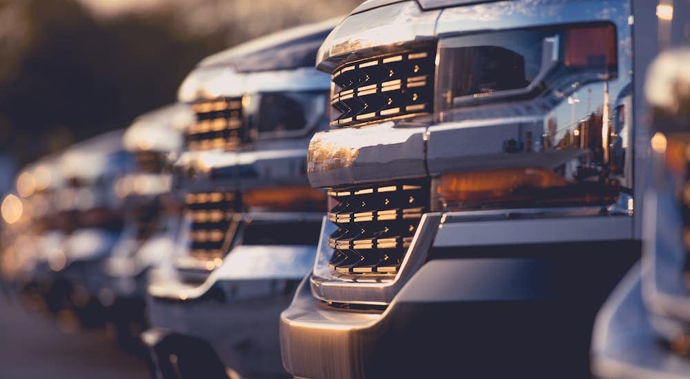 A closeup shows a line of grilles on used trucks on a used car lot near Lexington, KY.