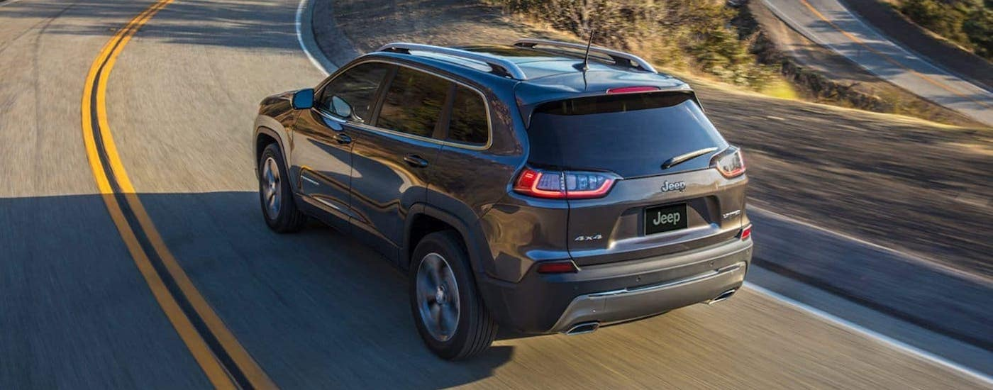 A gray 2020 Jeep Cherokee is driving on a winding road, shown from a high angle.