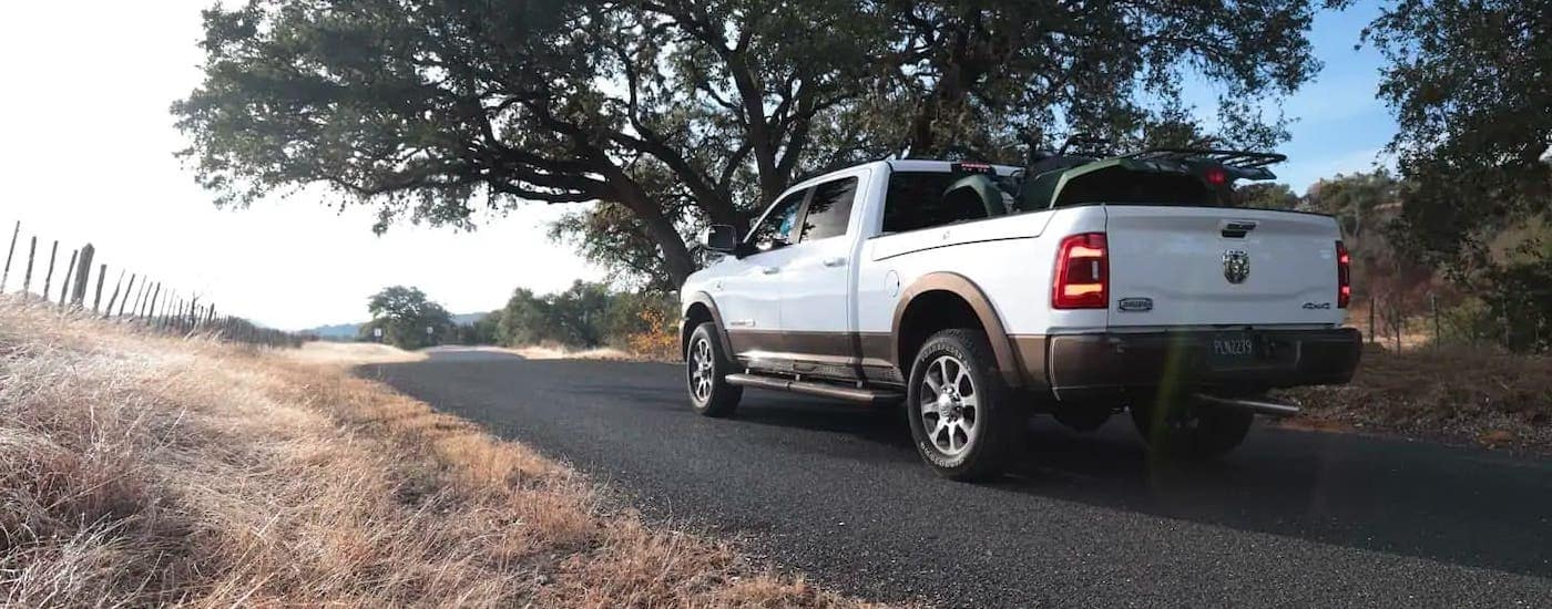 A white 2020 Ram 2500 is driving away on a highway past trees.