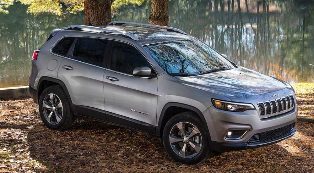 A silver 2020 Jeep Cherokee is parked in front of a pond.
