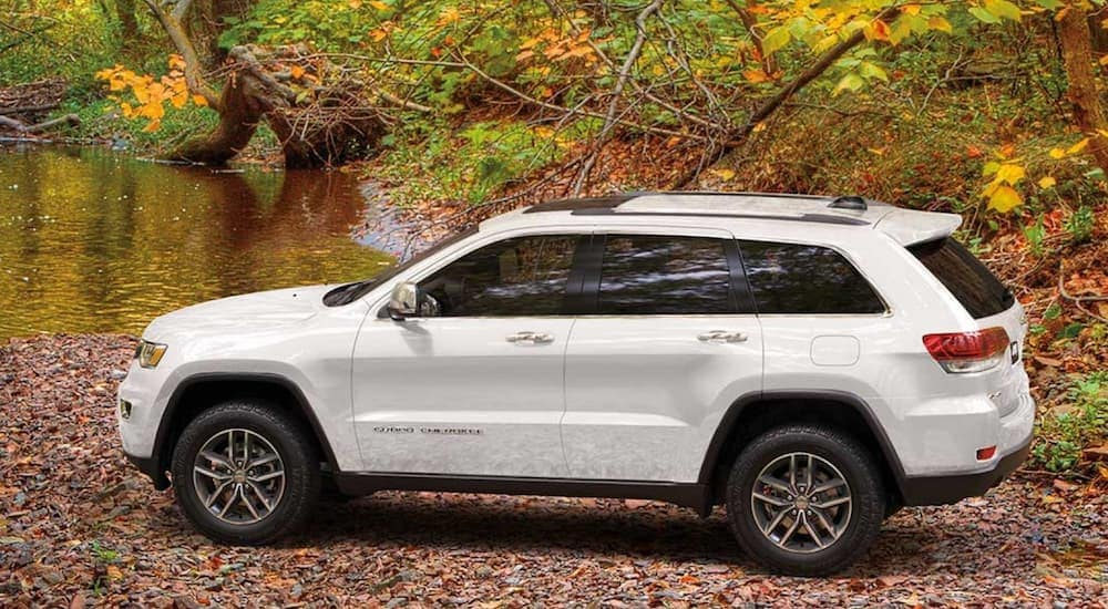 A white 2020 Jeep Grand Cherokee, popular among new vehicles for sale, is parked on a rocky river bank.