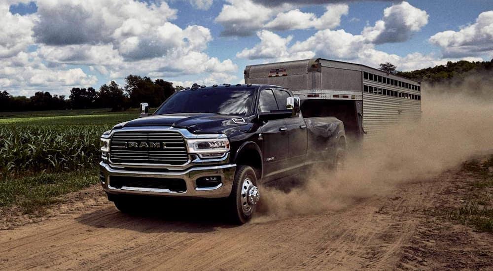 A black 2020 Ram 3500 is towing a horse trailer on a dirt road past fields near Lexington, KY.