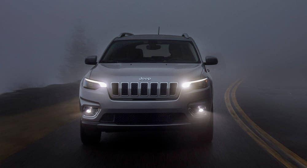 A grey 2019 Jeep Cherokee is driving on a dark foggy road near Lexington, KY.