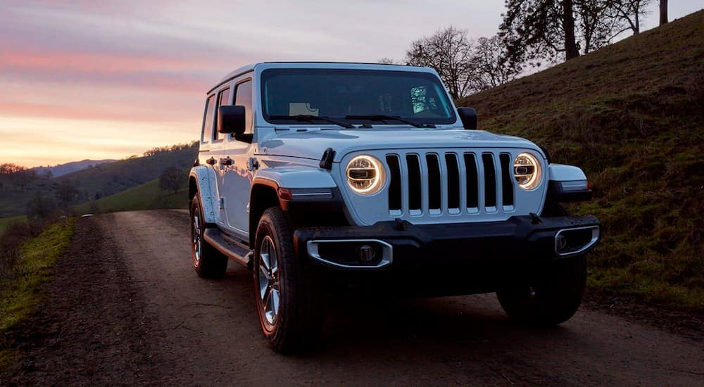 A white 2019 Jeep Wrangler Unlimited, popular among used cars, is driving on a dirt road just after sunset.