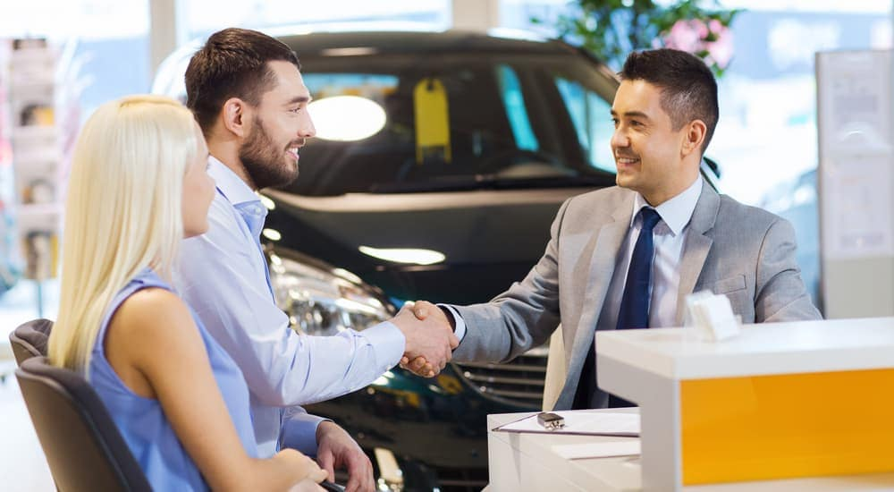 A salesman and buyer are shaking hands after the couple bought a car in a Lexington dealership.