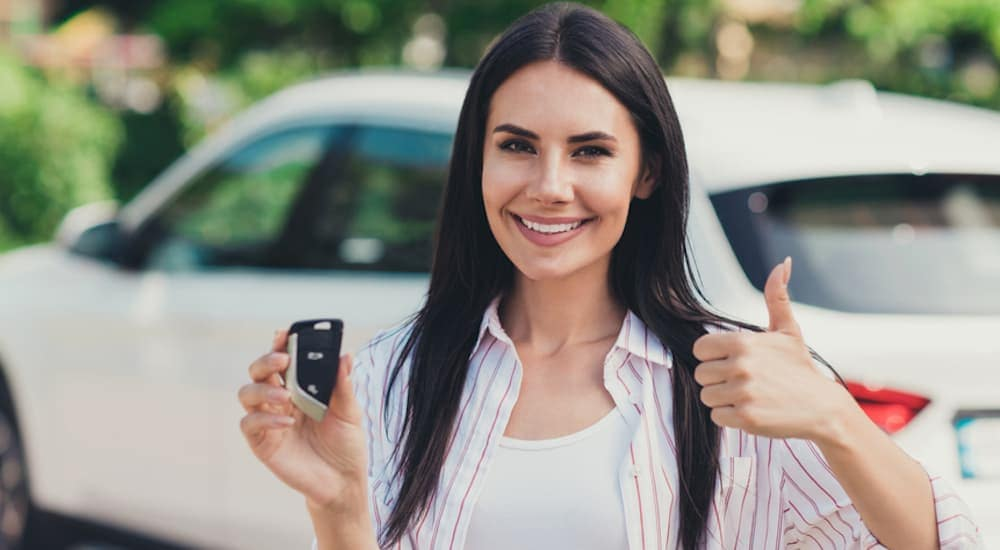 A woman is giving the thumbs up with the keys to a white car in the other hand.