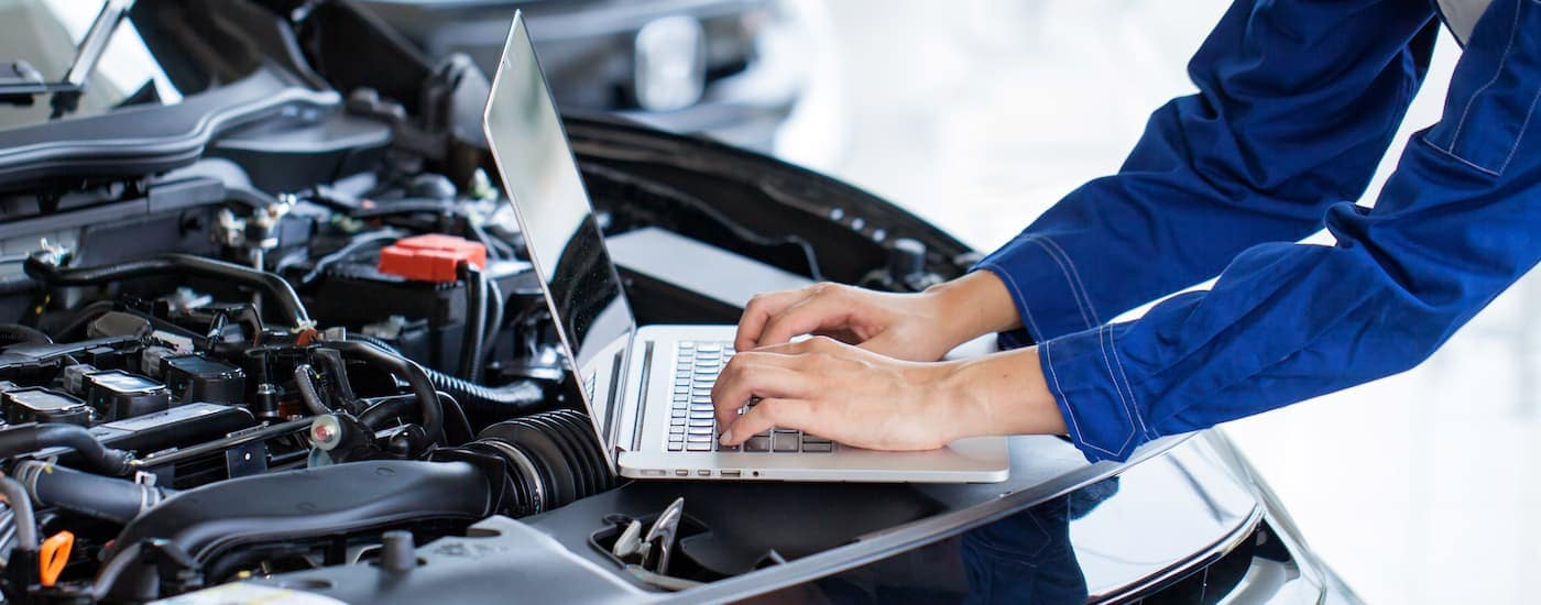A mechanic at a Lexington dealership is using a laptop on the engine bay of a vehicle.