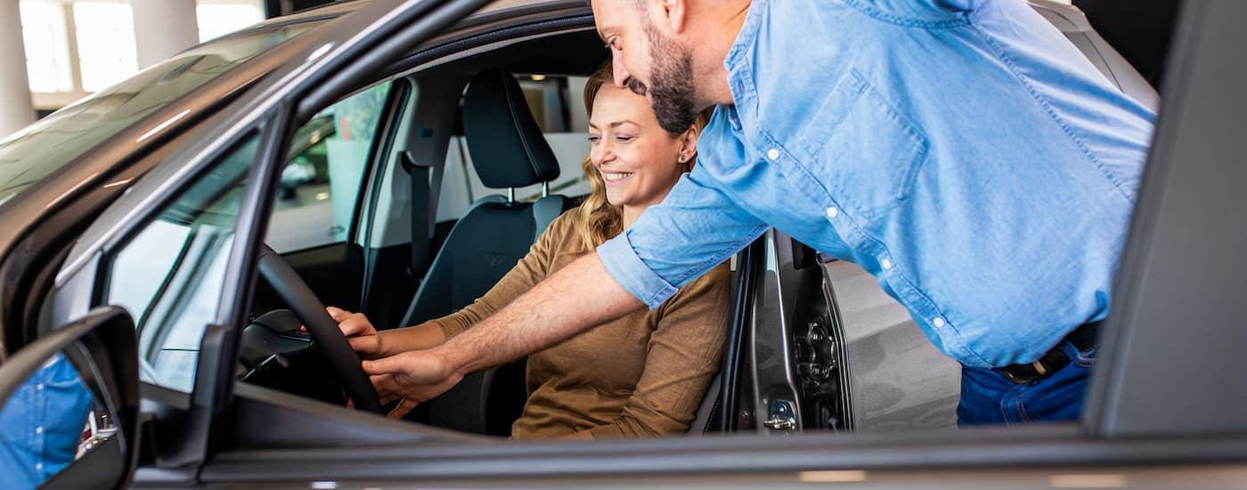 A salesman is showing a woman sitting in a car the features it has while she is looking at used cars near me.